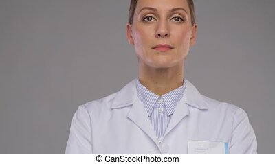 medicine, profession and healthcare concept - happy smiling female doctor or scientist in white coat with badge over grey background