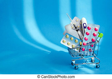 Medicines and pills in a shopping cart on blue background. Consumer buying panic about coronavirus covid-19 concept. First aid kit for home quarantine. Drug delivery.