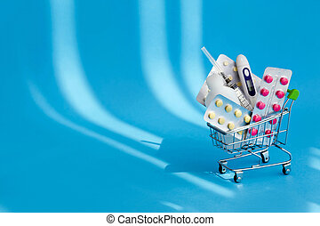 Medicines and pills in a shopping cart on blue background. Consumer buying panic about coronavirus covid-19 concept. First aid kit for home quarantine. Drug delivery. Copy space.