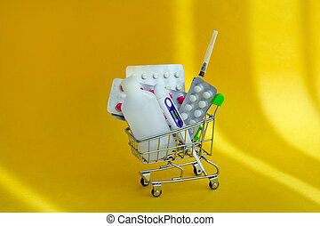 Medicines and pills in a shopping cart on yellow background. Consumer buying panic about coronavirus covid-19 concept. First aid kit for home quarantine. Drug delivery.