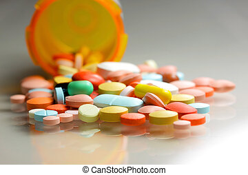 Medicines - Many colorful pills spilled from orange bottle