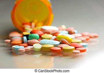 Medicines - Many colorful pills spilled from orange bottle