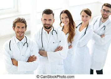 medicinsk hold, beliggende, hos, arme krydsede, på, en, hvid baggrund