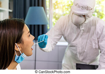 Medical staff with PPE suit test coronavirus covid-19 to asian woman by throat swab at home. New normal healthcare service at home and medical delivery concept.