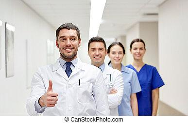 medics or doctors at hospital showing thumbs up