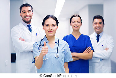 medics or doctors at hospital showing thumbs up -...