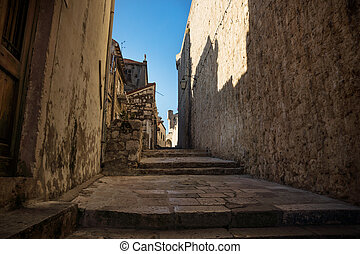 Medieval alley with shadows on fortress wall in Dubrovnik, Croatia