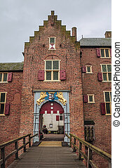 Medieval Ammersoyen Castle with its richly decorated entrance, brick walls and wooden bridge.