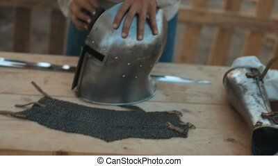 Medieval artisan polishes iron helmet to the high gloss for...