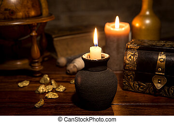 Medieval background with candles, a vintage wooden box, gold and a old globe