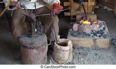 blacksmith working at smithy - medieval blacksmith working...