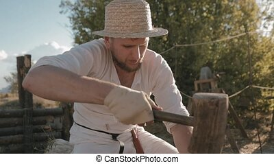 Medieval carpenter with the hammer and chisel carves from wood