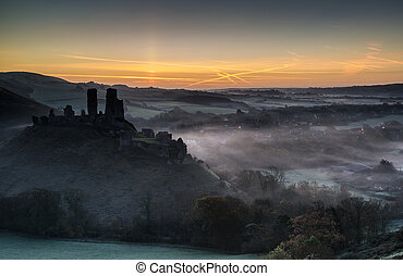 Medieval castle ruins with foggy landscape at sunrise -...