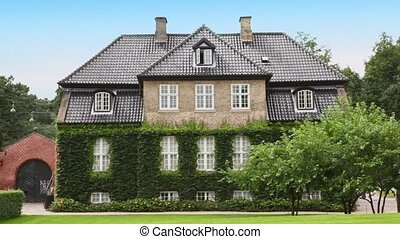 Medieval edifice with ivy on walls among trees in Copenhagen...