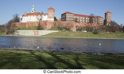 View across Vistula River to Wawel Hill with fortified Castle complex and belfry of Cathedral of Saints Stanislaus and Wenceslaus on sunny spring day, Krakow, Poland
