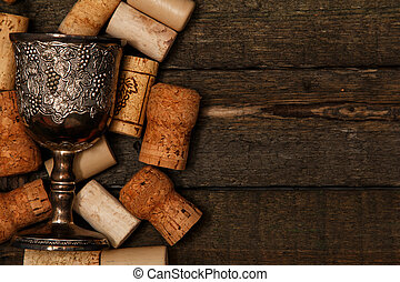 Medieval goblet and wine corks on wooden table