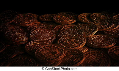 Closeup of old gold coins in firelight