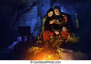 Medieval King in armor with sword is sitting on furs near the camp fire with his princess.