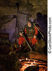 Medieval King in armor with the sword is sitting on furs near the camp fire and looking at fire.