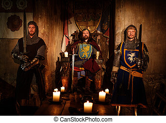 Medieval king with his knights in ancient castle interior.