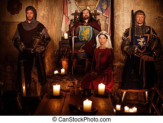 Medieval king with his queen and knights on guard in ancient castle interior.