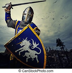 Medieval knight against hill full of crosses.