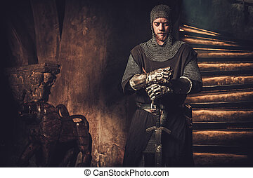 Medieval knight in ancient castle interior.