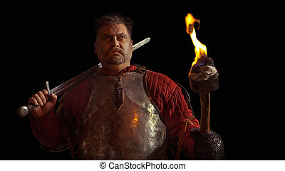 Medieval knight in the armor with the sword and flame. Isolated on black background.