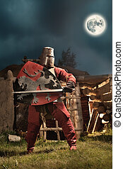 Medieval knight in the armor with the sword and shield