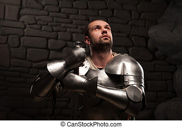 Medieval knight kneeling with sword - Closeup portrait of ...