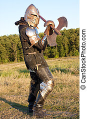 Medieval knight in the field with an axe