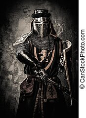 Medieval knight with a sword against stone wall
