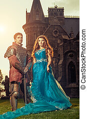 Medieval knight with his beloved lady. Ancient castle on the...