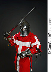 Medieval knight with sword and shield against gray wall