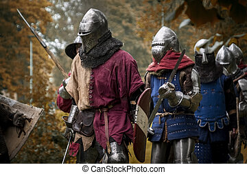 medieval knights on the march in the forest