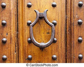 medieval knocker on old door in Florence city