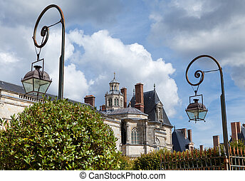 Medieval landmark royal hunting castle Fontainbleau near Paris in France and garden on the cloudy sky background