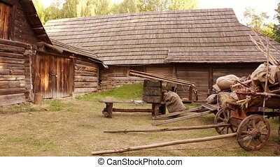 Medieval log cabin in the forest. Old medieval european farmhouse with carts of food.