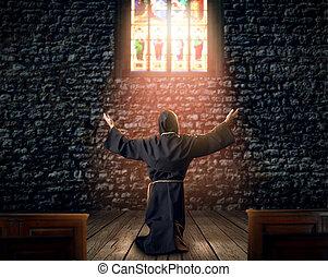 Medieval monk kneeling and praying in church
