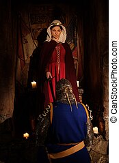 Medieval queen doing knighting ceremony in ancient castle...