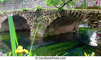 medieval stone bridge in eden colourful garden vibrant with...