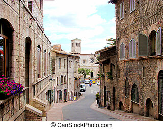Medieval street in Assisi, Italy and the church San Pietro