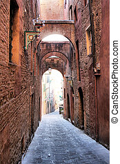Medieval street in Siena, Italy - Narrow medieval arched...