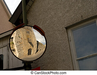 Traffic mirror in the picturesque town of Visby on then island of Gotland, Sweden, showning a part of the medieval surrounding wall