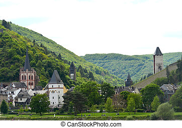 Medieval towers in a small German village, surrounded by hills.