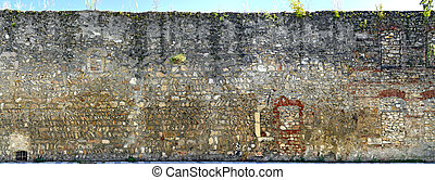 Medieval town wall with bricked doors and window breaches at...
