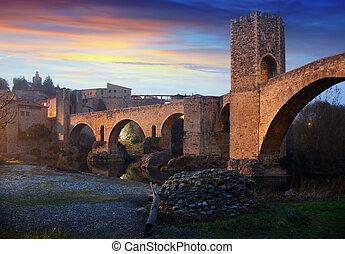 Medieval town with gate on bridge in evening. Besalu, ...