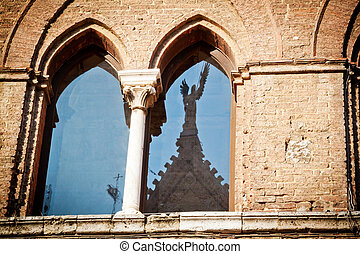The window of a medieval palace in Siena (Santa Maria della Scala) opposite the cathedral, with the stature of an angel reflected on the glass.