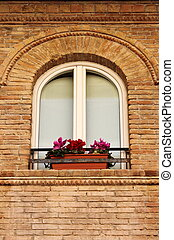 Medieval window with flowers pots in a red bricks wall building