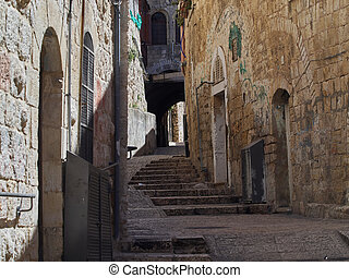 Medina in Jerusalem, a narrow street with steps in the Old City among the stone walls, Israel.